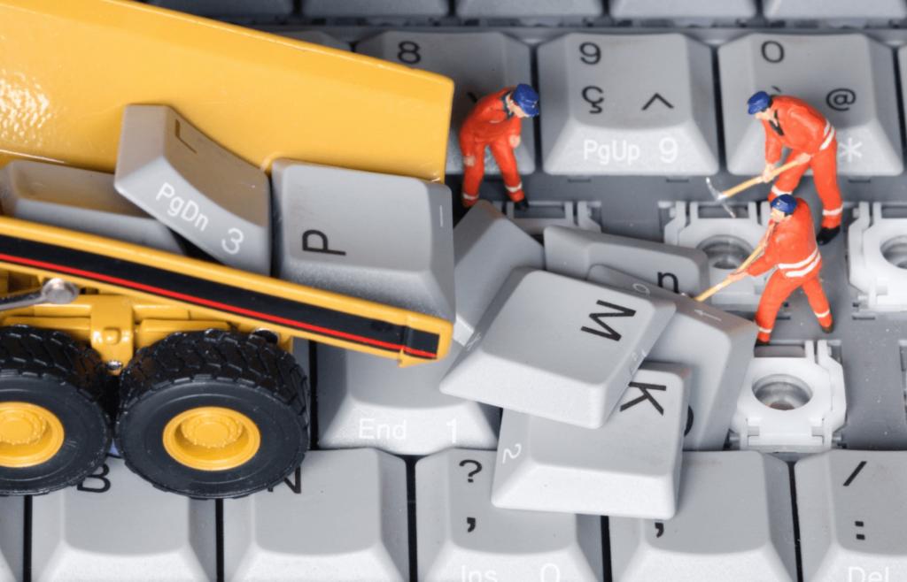 Figurines d'ouvriers retirant les touches d'un clavier d'ordinateur