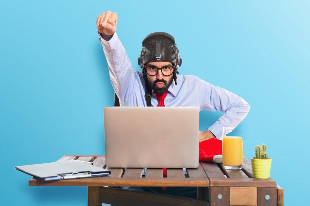 Homme déguisé en pilote devant un ordinateur