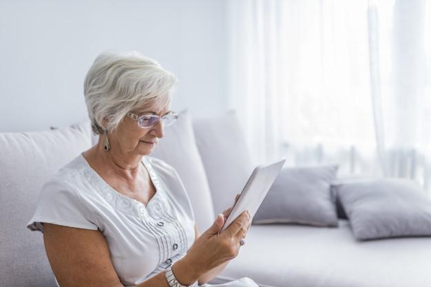 femme senior lisant des messages sur sa tablette